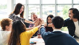 group of young multiethnic diverse people gesture hand high five, laughing and smiling together in brainstorm meeting at office. Casual business with startup teamwork community celebration concept.